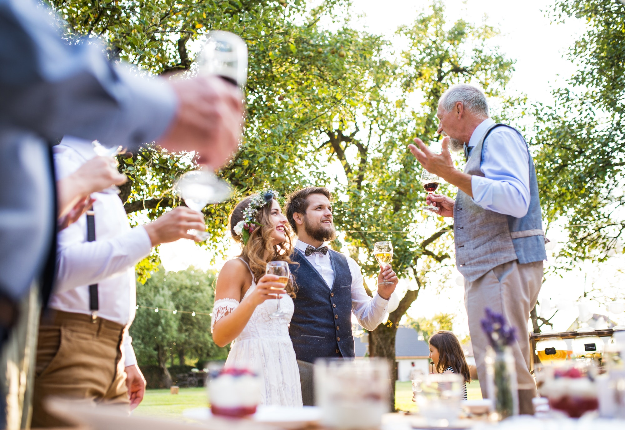 A senior man making speech at wedding reception outside in the background.